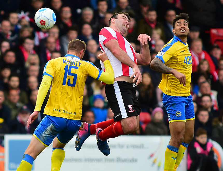 Lincoln City's Matt Rhead flicks on under pressure from Torquay United's Sean McGinty<br /> <br /> Photographer Andrew Vaughan/CameraSport<br /> <br /> Vanarama National League - Lincoln City v Chester - Tuesday 11th April 2017 - Sincil Bank - Lincoln<br /> <br /> World Copyright &copy; 2017 CameraSport. All rights reserved. 43 Linden Ave. Countesthorpe. Leicester. England. LE8 5PG - Tel: +44 (0) 116 277 4147 - admin@camerasport.com - www.camerasport.com