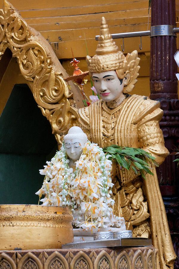 Myanmar, Burma.  Shwedagon Pagoda, Yangon, Rangoon.  Buddha Figure covered with Flower Garlands.  A Nat, a Buddhist spirit worshipped in Myanmar, stands guard behind.