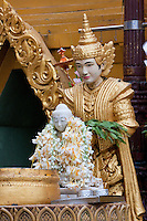 Myanmar, Burma.  Shwedagon Pagoda, Yangon, Rangoon.  Buddha Figure covered with Flower Garlands.  A Nat, a Buddhist spirit worshipped in Myanmar, stands guard behind.