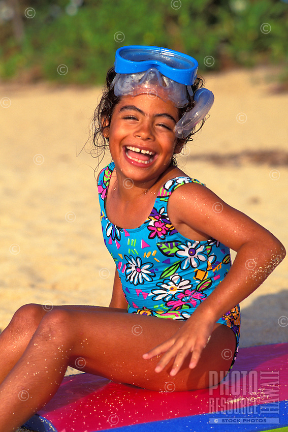 Little girl with snorkeling gear and boogieboard playing on the beach at the north shore