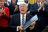 US President Donald J. Trump (C) shows an executive order entitled, 'Comprehensive Plan for Reorganizing the Executive Branch', after signing it beside members of his Cabinet in the Oval Office of the White House in Washington, DC, USA, 13 March 2017.<br /> Credit: Michael Reynolds / Pool via CNP