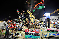 Men wave flags and shoot guns into the air as they celebrate at Martyrs' Square in Tripoli. After a six month revolution, rebel forces finally managed to break into Tripoli and have taken control of Bab al-Aziziyah, Col Gaddafi's compound and residence. Few remain that are loyal to Gaddafi in the city; it is seeming that the 42 year regime has come to an end. Gaddafi is currently on the run.