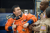 Houston, TX - (FILE) -- File photo from December 22, 2008.  Japan Aerospace Exploration Agency (JAXA) astronaut Koichi Wakata, STS-119 mission specialist, gets help in the donning of a training version of his shuttle launch and entry suit in preparation for a training session in the Space Vehicle Mock-up Facility at NASA's Johnson Space Center. United Space Alliance suit technicians Andre Denard and Toni Cost-Davis assisted Wakata, who is scheduled to join Expedition 18 as flight engineer after launching to the International Space Station with the STS-119 crew..Credit: James Blair - NASA via CNP
