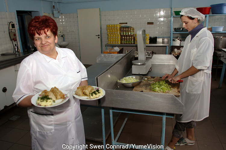 The Chief of the cooking team showing the midday menu. .In the kitchen of the URiC Radom Centre there are 4 of polish personnel who prepare daily fresh food for 230 refugees..Per person for the midday meal: one leaf of cabbage with chicken meat and herbs, boiled potato, fried onion, soup, fruit juice, stewed apples for the dessert and  bread..-For security reason, the face of the adult asylum seeker have been evicted of the photography..-For security reason, the names of the adult asylum seeker have been change. .-Article 9 of the Act of 13 June 2003 on grating protection on the Polish territory (Journal of Laws, No 128, it. 1176) personal data of refugees are an object of particular protection..-Cases where publication of a picture or name of asylum seeker had dramatic consequences for this persons and is family back in Chechnya. .Please have safety of those people in mind. Thank you.