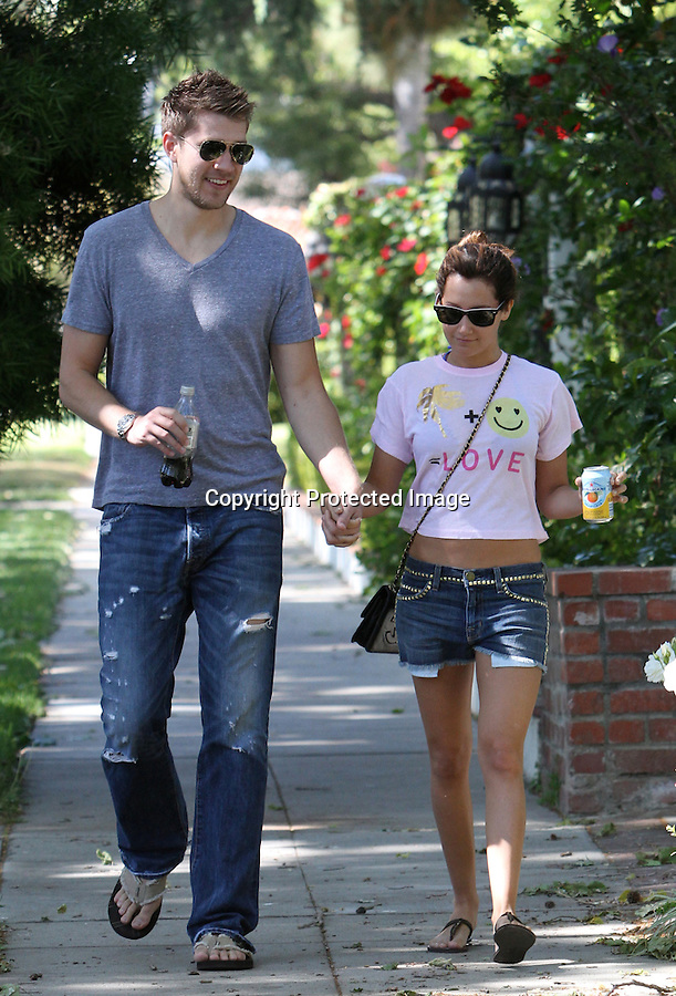 4-30-2010...Ashley Tisdale wearing a yellow happy face t-shirt that says love on it while walking in Los Angles with her boyfriend Scott Speer. Ashley was also wearing daisy duke jean shorts with the pockets hanging out. ...AbilityFilms@yahoo.com.805-427-3519.www.AbilityFilms.com