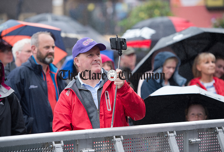 Ken O Heiligh recording a performance on his phone in Abbey Street car Park during a wet final Sunday of the All-Ireland Fleadh in Ennis. Photograph by John Kelly.