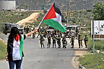 A Palestinian protester waves her national flag in front of Israeli security forces during a protest marking the Palestinian Land Day in the West Bank village of Nabi Saleh near Ramallah, March 28, 2015. Land Day commemorates the unrest that erupted in March 1976 when Israeli Arabs protested the Israeli government's confiscation of thousands of acres of Arab-owned land and in which six Arab citizens were killed by Israeli police. Photo by Shadi Hatem