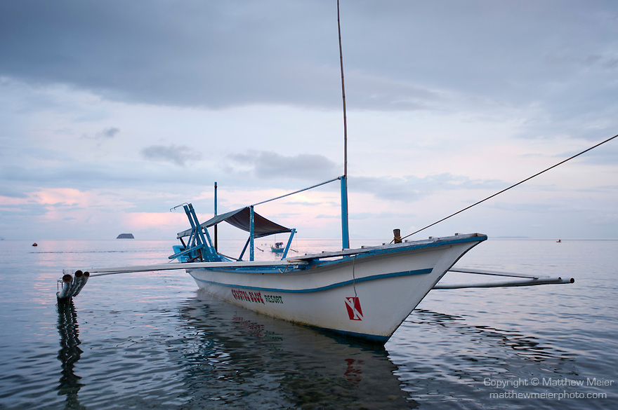 Anilao, Philippines; a Banca, or outrigger boat, is anchored along shore in the early morning, predawn sunrise with colorful clouds in the background