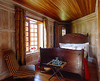 A large antique French bed dominates this small wood-panelled bedroom