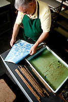 Master craftsman, artisan Enrico Gannini creating hand crafted 'marbled' paper, made from a preparation of paint and extract of seaweed, in his workshop (bottega) on Via dei Velluti, Florence, Italy
