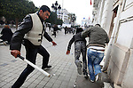 Police ran after protesters with clubs, trying to disperse the crowds, in downtown Tunis, Tunisia, Jan. 18, 2011. The Tunisian police and army struggled to maintain order in the capital, as thousands of protesters once again filled the streets.