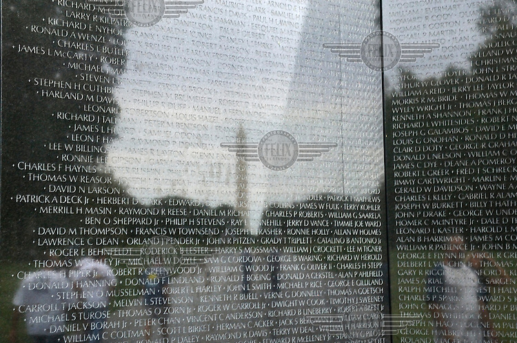 The black marble Vietnam War Memorial in Washington DC, inscribed with the names of the soldiers who died, with a reflection of the Washington Monument.