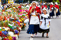 A woman walks with his daughter before to take part on the 58th Silleteros' parade in the framework of the flowers' fair, this year the silleteros parade was declared intangible heritage of Colombia. Medellín, Colombia 09/08/2015