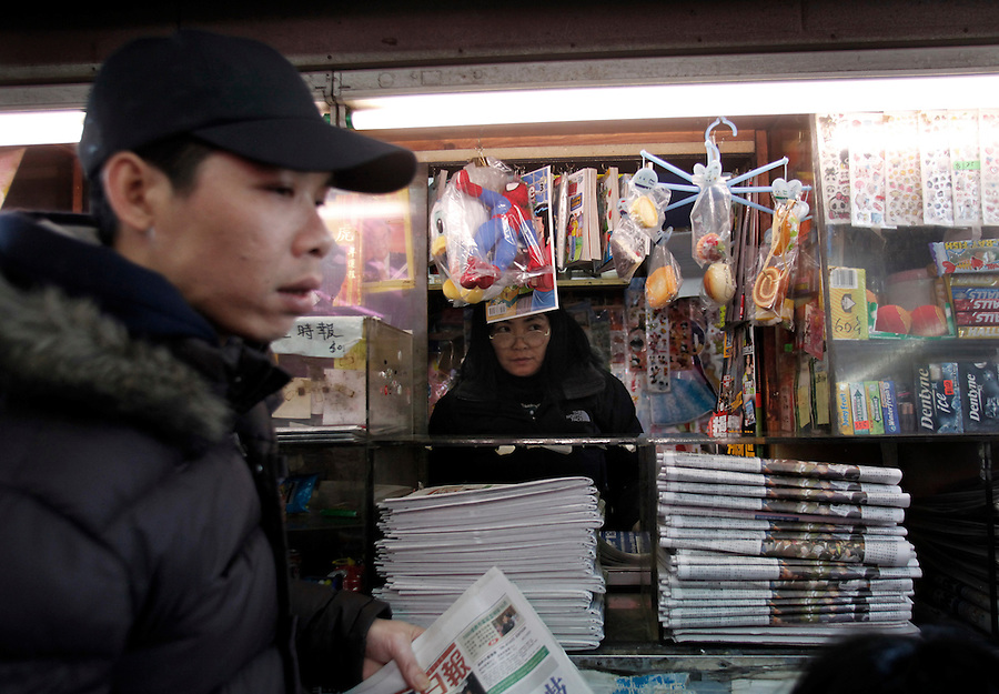 A woman sells newspapers at a kiosk in Chinatown in New York City.
