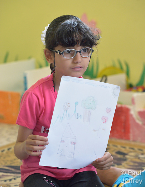 A girl shares her drawing during a group activity at the Youth Empowerment Center in Beit Hanoun, Gaza. The program is supported by Caritas and DanChurchAid, a member of the ACT Alliance, and is designed to help children better cope with the trauma they experienced during the 2014 war.<br />