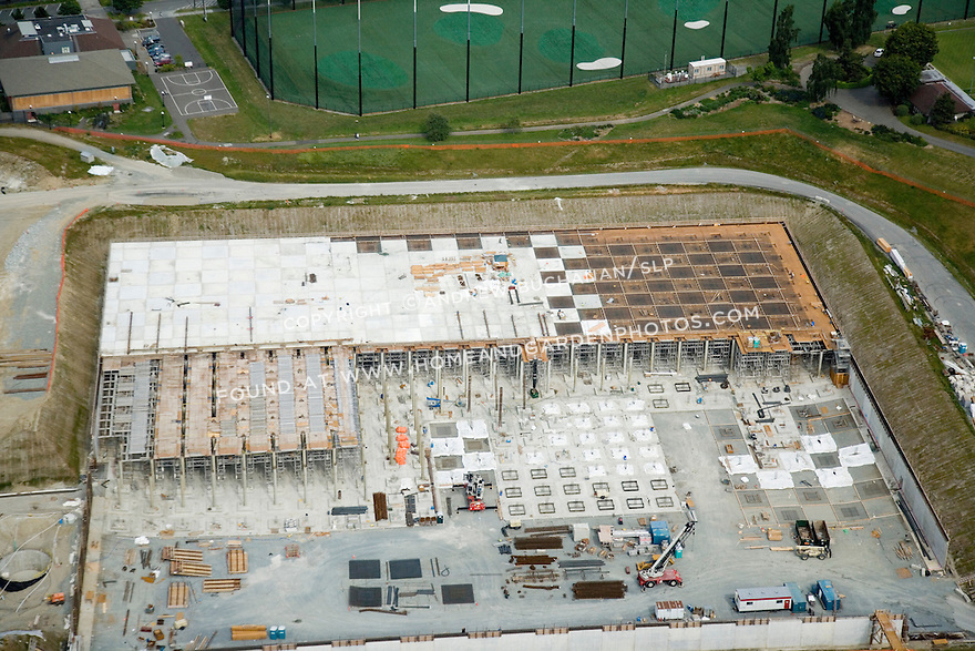 An aerial view of a commercial construction project to cover, or lid, the Jefferson Park reservoir in Seattle's Beacon Hill neighborhood.  Tall columns supporting a partially completed roof can be seen covering roughly half the reservoir space, with various construction equipment and materials scattered about the site.  When completed, the roof will host a park and other green space for neighborhood residents, while the reservoir below helps supply fresh water for Seattle.