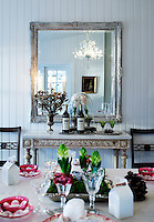 A Venetian crystal chandelier which hangs above the Christmas dining table is reflected in a silver-gilt framed mirror