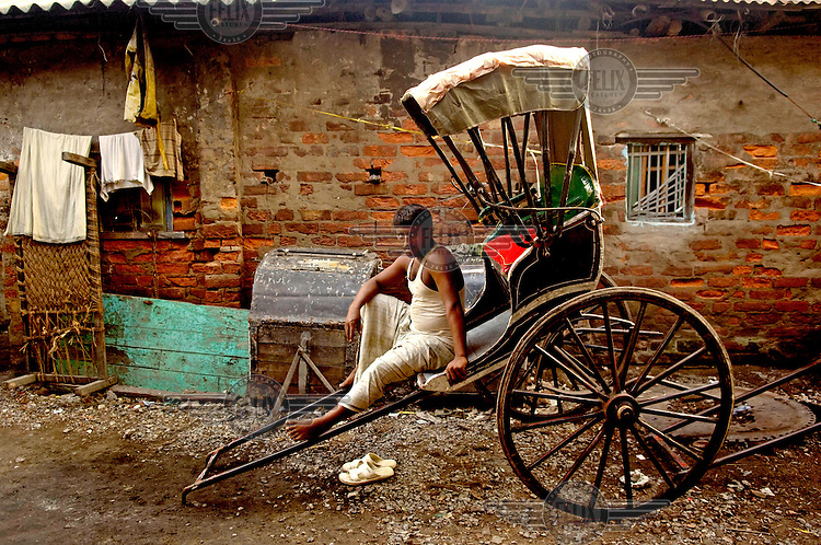 A rickshaw puller takes a break from his work. Despite numerous atempts to ban them Kolkutta remains the only place in India where hand drawn rickshaws are still found.
