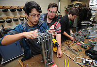STAFF PHOTO ANDY SHUPE - Juan Zuniga, 15, left, and Brayden Rose, 16, replace parts on a robot component as Noah Wehn, 16, right, assembles a  part while working on the team's robot Thursday, Dec. 18, 2014, at Southwest Junior High School in Springdale. The students are sophomores at Har-Ber High School, but drive to Southwest Junior High School to use the school's workroom since Har-Ber lacks a similar facility.