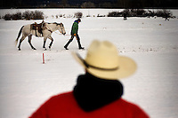 A man watches as a competitor walks a horse through the course at the Whitefish Skijoring World Championship event in Whitefish, Montana, USA.  Skijoring is a competitive sport in which a person on skis navigates an obstacle course while being pulled behind a galloping horse.