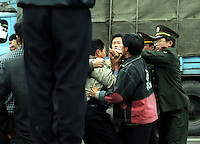 A man is arrested as farmers block a road just outside Chongqing in Sichuan Province, China. The farmers were complaining about police corruption and failure to pay compensation for land taken from them by the local government.
