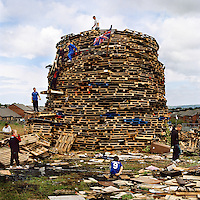 Youths in the loyalist Upper Ardoyne part of Belfast continue in the tradition of building a bonfire to be set alight on the evening of 11 July each year. This event - the '11th Night' - marks the official start to the July celebrations. It is followed by 'The Twelfth' (also known as Orangemen's Day) which celebrates the 'Glorious Revolution' of 1688 (when Protestant king William III ascended the English throne) and the Battle of the Boyne (when William III defeated the catholic claimant James on the east coast of Ireland). Young people in Protestant estates such as this spend weeks scavenging for wood and other materials used to build the structure and even stand watch in the evenings leading up to July 11th as they fear that the it may be attacked and destroyed by rival Catholic youths.
