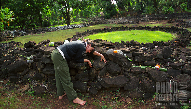 Woman making an offering at Keaiwa, Hawaiian healing heiau, a 15th century healing temple surrounded by a network of hiking trails in a magical forest, Aiea heights, Oahu