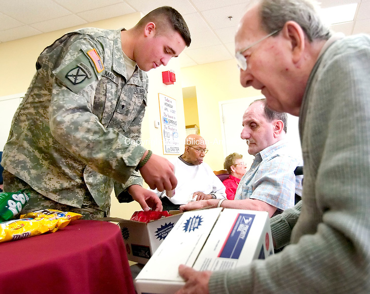 PROSPECT, CT. 05 April 2007-040507SV03--From left, Jeremy Mack, 19, of New Milford, a medic in the Army, packs up supplies and gifts that he will bring back to Iraq with him. World War II vets, Airforce Airman Second Class Ray LaBonte and Army Tec. Sgt. Warren Gould help him pack the items at Marathon Health Care in Prospect Thursday.<br /> Steven Valenti Republican-American