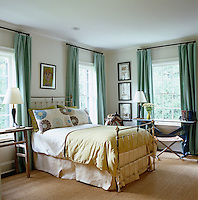 A distressed wrought-iron bed fits between the two windows dressed in Belgian linen curtains