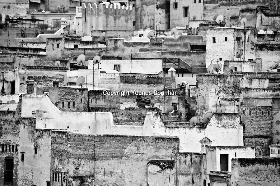 View of the city of Fes from above, showing details of rooftops. Modern satellites contrast with the old and decrepit walls of the city