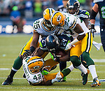 Seattle Seahawks running back Marshawn Lynch (24) is tackled by Green Bay Packers safety Morgan Burnett (42), linebacker James Lattimore (57) and defensive end Datone Jones (95) after rushing for a 21-yard gain in the NFL Kickoff held at CenturyLink Field September 4, 2014 in Seattle.  Lynch rushed for 110 yards and score two touchdown as  Seattle beat Green Bay 36-16. ©2014  Jim Bryant Photo. ALL RIGHTS RESERVED.