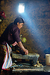 Audelina Vasquez Lopez, a Maya Mam woman, grinds corn for making tortillas and tamales in her home in Tuixcajchis, a small village in Comitancillo, Guatemala.