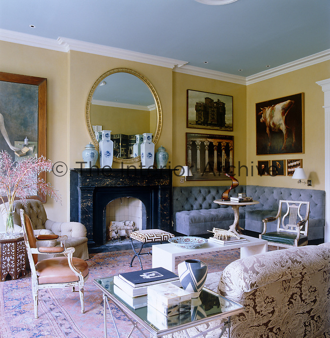 In the living room a grey button-backed banquette takes up an entire wall and corner next to the black marble fireplace