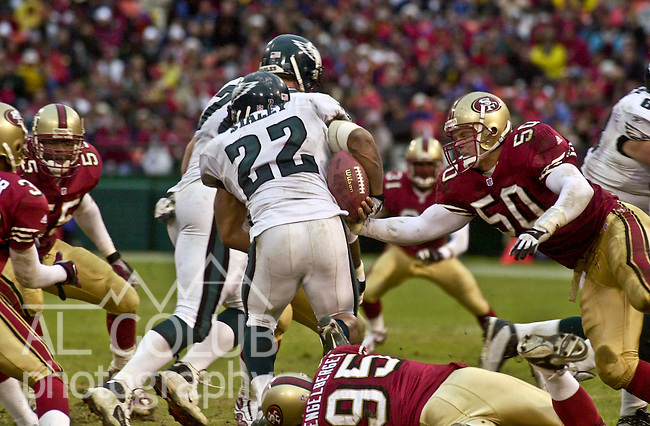 San Francisco 49ers linebacker Derek Smith (50) strips ball from Philadelphia Eagles running back Duce Staley (22) on Saturday, December 22, 2001, in San Francisco, California. The 49ers defeated the Eagles 13-3.