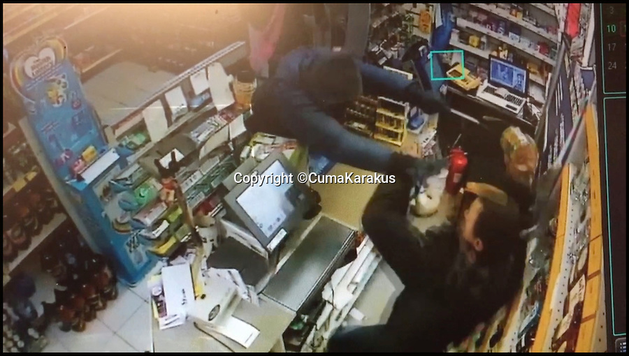 BNPS.co.uk (01202 558833)<br /> Pic: CumaKarakus/BNPS<br /> <br /> The moment the robber lunged for Cuma.<br /> <br /> This is the dramatic movement a heroic shopkeeper scared off a knife-wielding raider by launching a glass jar of dog biscuits at him. <br /> <br /> Brave Cuma Karakus dodged the masked thug's eight inch blade as he jabbed over the counter armed only with the treats he keeps for customers' pets. <br /> <br /> The dad of two then incredibly threw it at the crook as he tried to run around the table, appearing to hit a glancing blow on his hand.