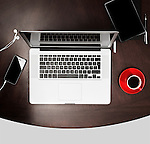 Apple macbook laptop computer, iPhone, Kindle tablet and a red cup of coffee on a desk. Working or studying environment concept. High angle view isolated on gray background.