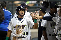 Third baseman Jose Brizuela (20) of the Columbia Fireflies is greeted by teammates in the dugout after scoring a run during a game against the Charleston RiverDogs on Tuesday, August 28, 2018, at Spirit Communications Park in Columbia, South Carolina. Columbia won, 11-2. (Tom Priddy/Four Seam Images)