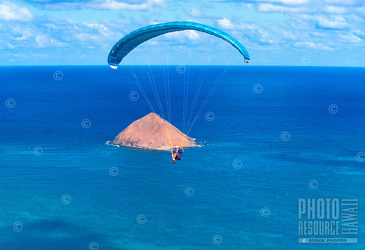 A paraglider enjoys riding the warm updrafts over the Moku Lua islands and Lanikai beach on Oahu's windward side. This view is from the Lanikai Ridge Trail.