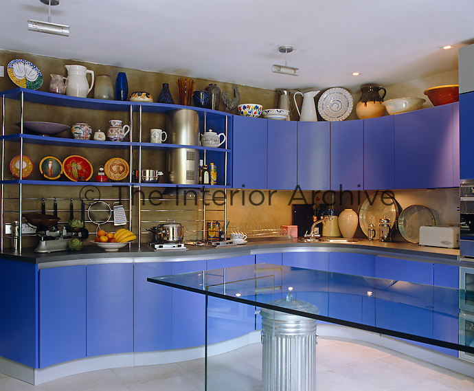 The walls of this small kitchen are lined with curved blue kitchen units while the central table is of glass