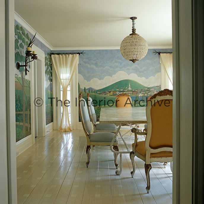 The dining room walls are covered in a mural by Lyndon Andrews that recalls the landscapes of 19th century New England painter Rufus Porter