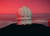 Canada-France-Hawaii Telescope seen in the light of the Full Moon, and illuminated from behind by the vivid red sunset caused by dust in the atmosphere from the eruption of Mt. Pinatubo.  Mauna Kea Observaory, Hawaii.