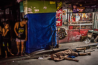 "MANILA, PHILIPPINES - OCTOBER 02: The body of Michael Araja, 29, an alleged drug user lays in front of ""sari sari"" a local convenience store, after being gunned down in the street by unidentied men in a ""riding-in-tandem"" killing in the early hours of October 02, 2016 in Manila, Philippines. According to neighbors, two unidentified men on a motorcycle, stopped as Mr Araja, had left his home to buy cigarettes and a drink for his wife, and gunned him down as he stood in front of his local convenience store. This type of murder perpetrated two peope on a motobike, is commonly referred to as a ""riding-in-tandem"" killing.  <br /> Photo by Daniel Berehulak for The New York Times"