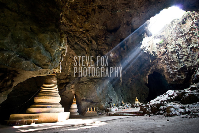 Buddha images and a pagoda inside the Tham Khao Luang cave are illiminated by a hole in it's ceiling, Phetchaburi, Thailand.