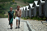 "Two girls walk along a street in a model resettlement village constructed by the Lutheran World Federation in Gressier, Haiti. The settlement houses 150 families who were left homeless by the 2010 earthquake, and represents an intentional effort to ""build back better,"" creating a sustainable and democratic community."