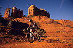 A mountain biker rides a trail below Cathedral Roack in Sedona, Arizona.