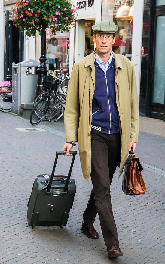 Nederland, Utrecht, 10 okt 2014<br /> Mensen op straat. Man in regenjas en met aktentas loopt richting het station. Komt waarschijnlijk van zijn werk. <br /> Foto: (c) Michiel Wijnbergh