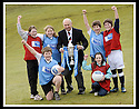 24/02/2009  Copyright Pic: James Stewart.File Name : sct_jspa10_scottis_cup.FORMER FALKIRK LEGEND ALEX TOTTEN SHOWS OFF THE HOMECOMING SCOTLAND SCOTTISH CUP TO (l to r rear) REBECCCA LEWIS, SARAH JOHNSTON, IAN MCARTHUR, ROSS ANDERSON (l to r front) STUART IRVINE AND CAITLIN MUNGALL, PRIMARY SEVEN PUPILS AT ST MARGARET'S PRIMARY SCHOOL, POLMONT......Press Release..... A unique interactive tour to engage primary school children with football and the Homecoming Scottish Cup rolls into town today, Tuesday 24 February 2009 at St Margaret's Primary School in Falkirk.  . .Up to 100 pupils in primaries 5 to 7 at each local school will receive specialist skills and drill training from Scottish Football Association coaches as well as getting the chance to view the Homecoming Scottish Cup trophy itself.. .The school tour takes the form of a giant 'football-shaped' tent, which houses the world's oldest footballing trophy and information about Homecoming Scotland and the Scottish Cup tournament.. .Future football stars will be given soccer skills training ahead of watching their home team, Falkirk, take on Inverness Caledonian Thistle in the quarter finals of the Homecoming Scottish Cup on the weekend of 7 March.. .Falkirk legend Alex Totten, who used to manage the side, will be on hand at St Margaret's Primary School to share his knowledge and experience with the kids and to see the trophy himself.. .All primary schools in Scotland will also be sent education packs to encourage pupils to know more about Homecoming Scotland and to learn more about healthy eating, fitness and playing football as a way to keep fit and have fun.  . .As part of the football celebrations, the tour will then encourage locals in the town centre to get behind their local team, when the cup visits The Mall in Falkirk later in the afternoon.. .The Homecoming Scottish Cup Tour has been designed to engage with Scotland's local communities and spread the message about joining in the celebrations for Homecomi