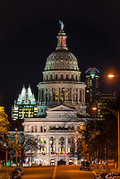 This a vertical view of Capitol of Texas at night view from MLK street.  You can see the Frost building and the Austonian in the background.