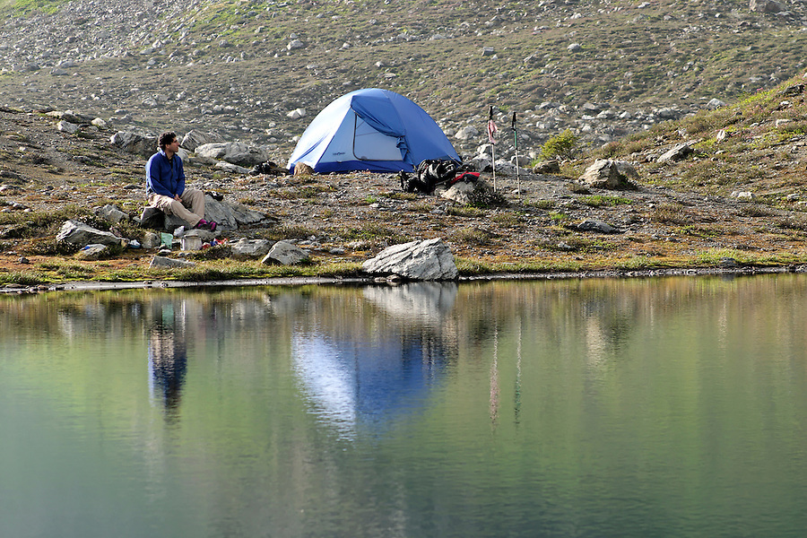 Man sitting beside tent and alpine lake, near Yellow Aster Butte, North Cascades, Whatcom County, Washington, USA
