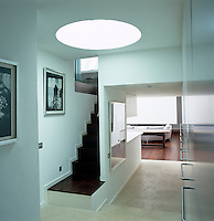 A circular skylight is a luminous feature above the modest staircase of this entrance hall